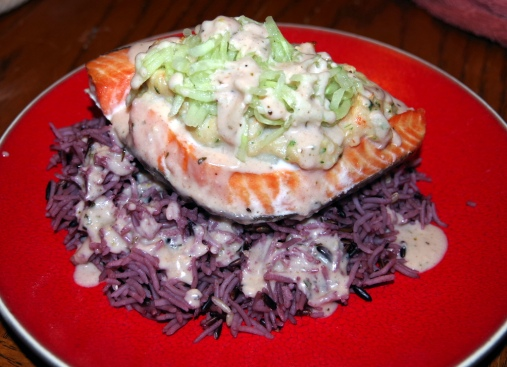 plated stuffed salmon on rice with cucumber and sauce