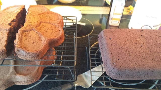two chocolate cakes cooling on racks